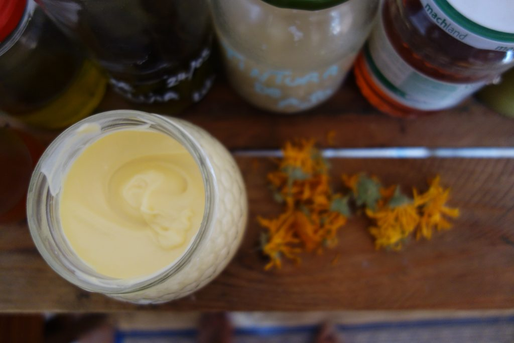 Jar of natural moisturiser with calendula flowers